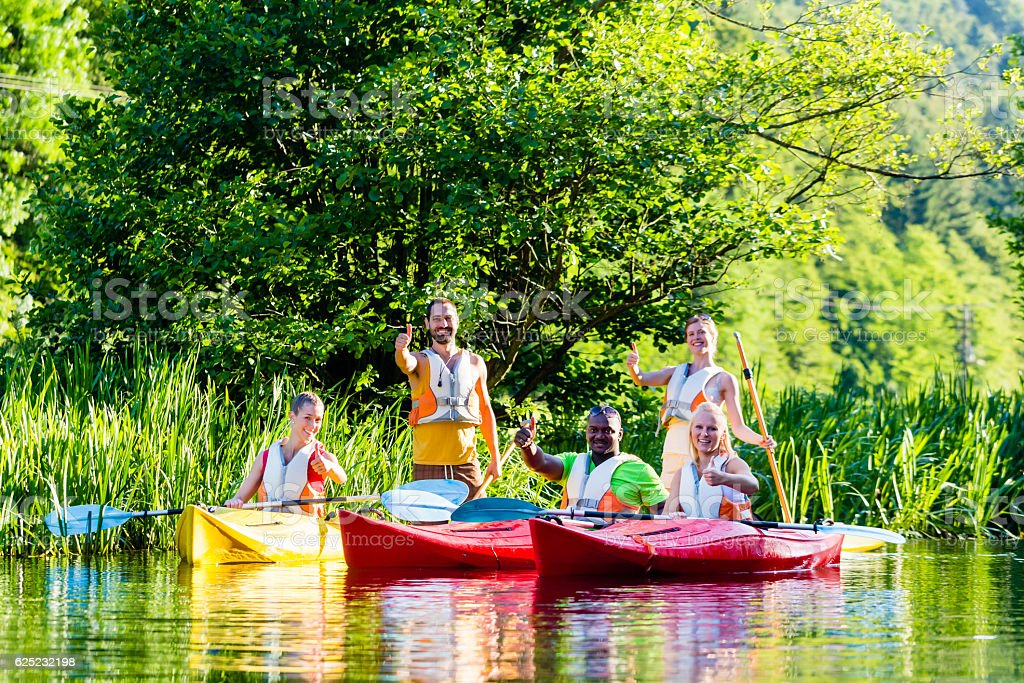 Friends driving with kayak on forest river stock photo