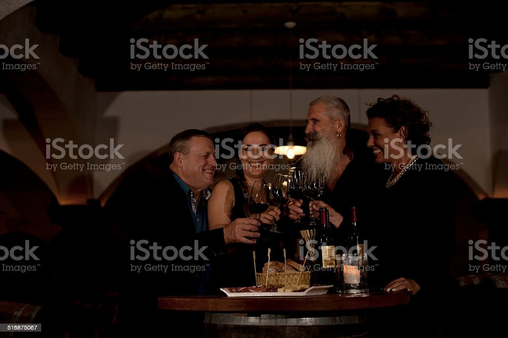 Friends Eating and Drinking in Wine Cellar stock photo