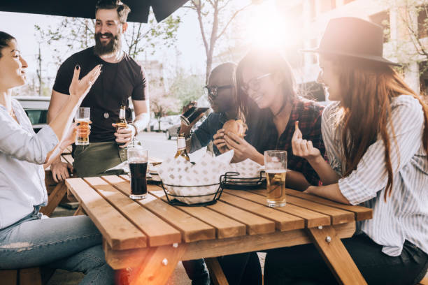 friends eating and drinking outdoors and having fun - flare foto e immagini stock