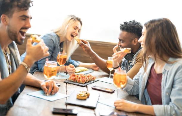 패션 칵테일 바 레스토랑에서 스프리츠를 먹고 마시는 친구들 - 펍에서 해피 아워에서 음료와 음식과 함께 즐거운 시간을 보내는 젊은이들과의 우정 개념 - 피자 슬라이스에 집중 - 식전 반주 뉴스 사진 이미지