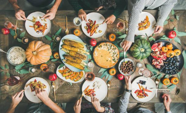 amigos comiendo en la mesa del día de acción de gracias con comidas vegetarianas - vegana fotografías e imágenes de stock