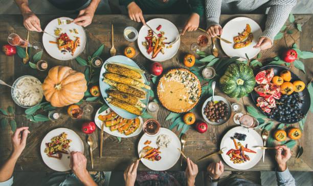 friends eating at thanksgiving day table with vegetarian snacks - jedzenie wegetariańskie zdjęcia i obrazy z banku zdjęć