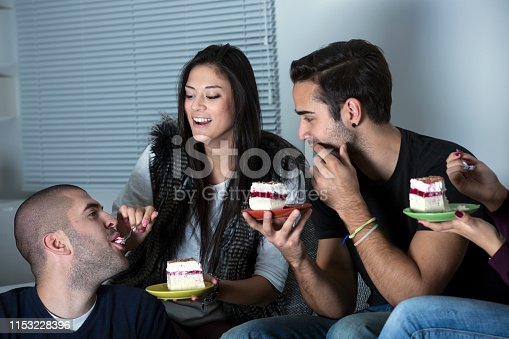Friends hanging out at home, eating a cake. Two females and two males, all Caucasian about 20 years old.