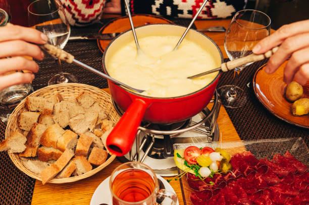 Freunde essen Käsefondue in einem gemütlichen traditionellen Schweizer Restaurant – Foto