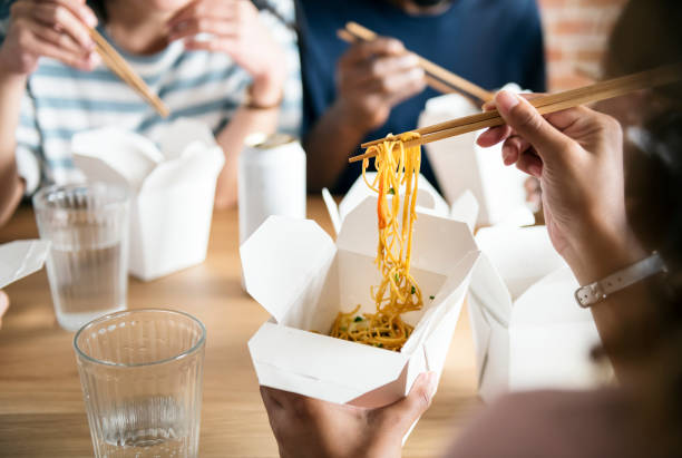 Friends eating Chow mein together Friends eating Chow mein together chinese takeout stock pictures, royalty-free photos & images