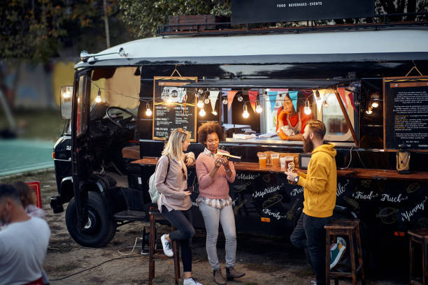 friends eating, drinking, talking, socializing outdoor in front of modifed truck for fast food service stock photo