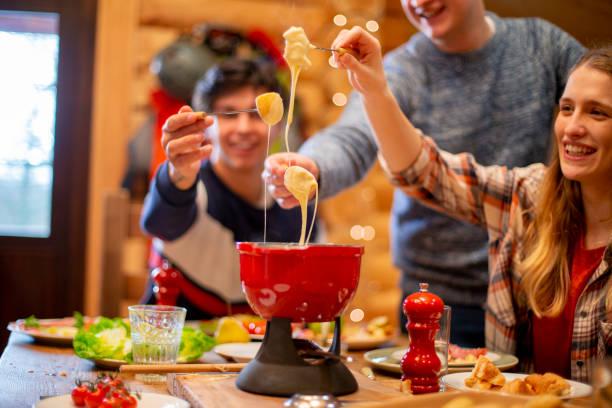 freunde essen fondue beim abendessen - fondue stock-fotos und bilder