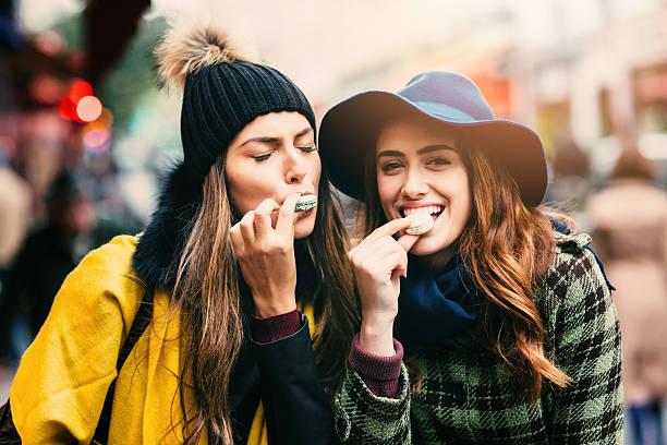 amis manger macarons à paris - mode paris photos et images de collection