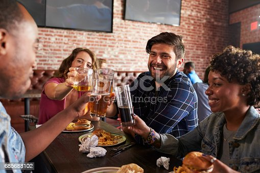 istock Friends Eating Out In Sports Bar With Screens In Background 685688102