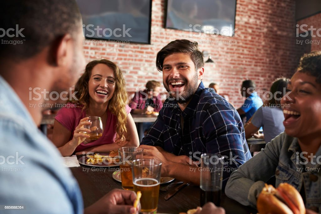 Friends Eating Out In Sports Bar With Screens In Background royalty-free 스톡 사진