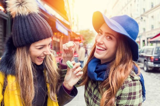friends eating parisian macaroons - genießen französisch stock-fotos und bilder