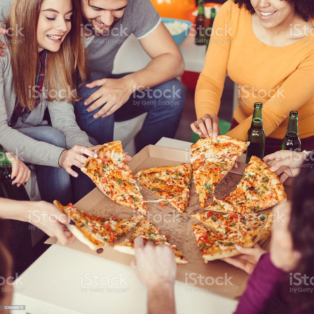 Amis manger pizza à la maison - Photo