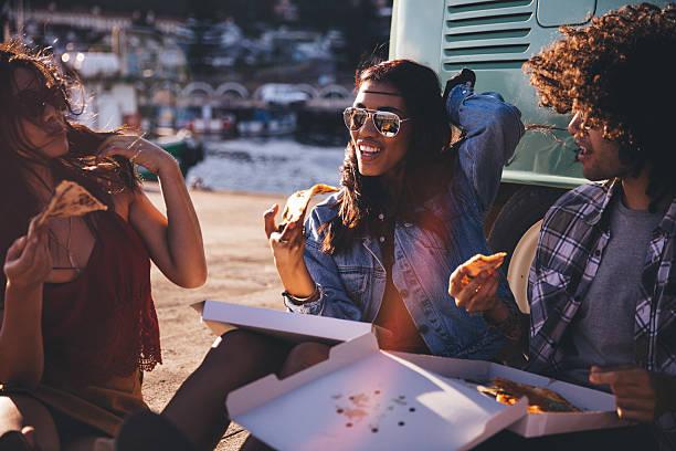 Amigos comendo pizza no porto próximo ao vintage Van - foto de acervo
