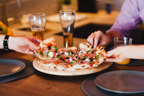 Friends eating pizza at the table stock photo