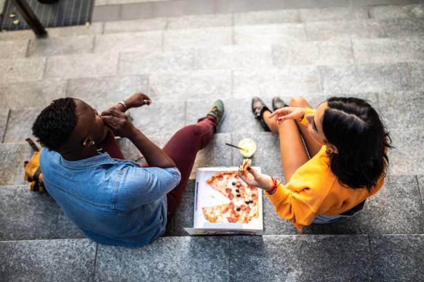 amigos comiendo pizza al aire libre - couple lunch outdoors fotografías e imágenes de stock