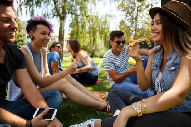 freunde essen pizza außerhalb - mensch isst gras stock-fotos und bilder