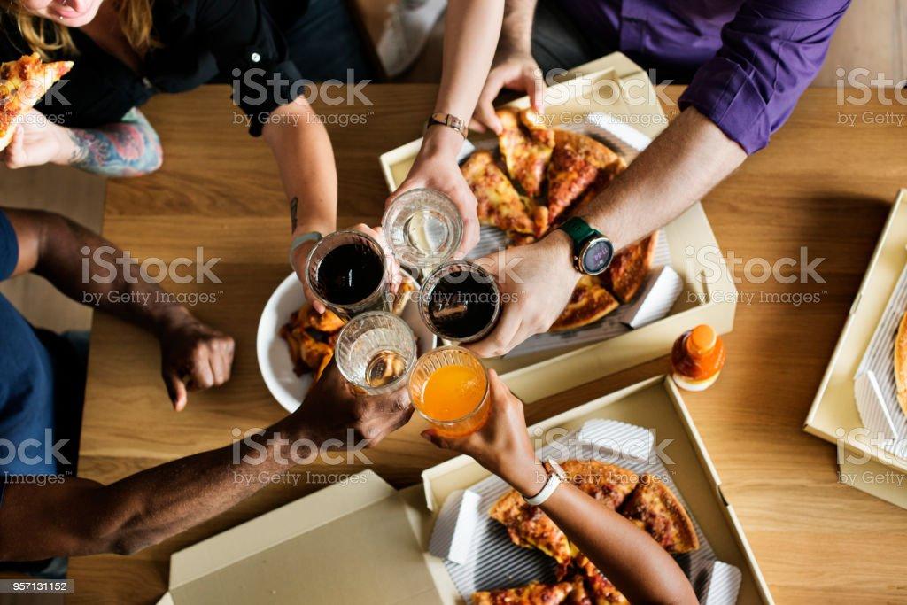 Amis, manger pizza ensemble à la maison photo libre de droits
