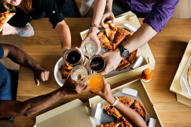 freunde zu hause zusammen pizza essen - schnellkost stock-fotos und bilder