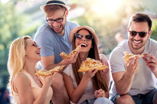 Friends eating pizza together stock photo