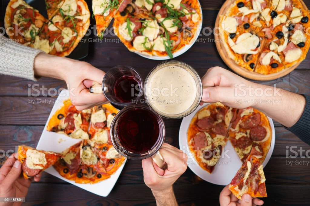 Friends eating pizza. Top view on male hands clinking mugs with stock photo