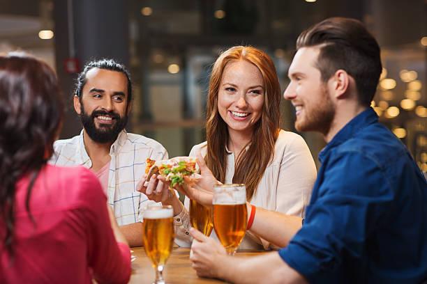 Amigos comendo pizza com cerveja no restaurante - foto de acervo