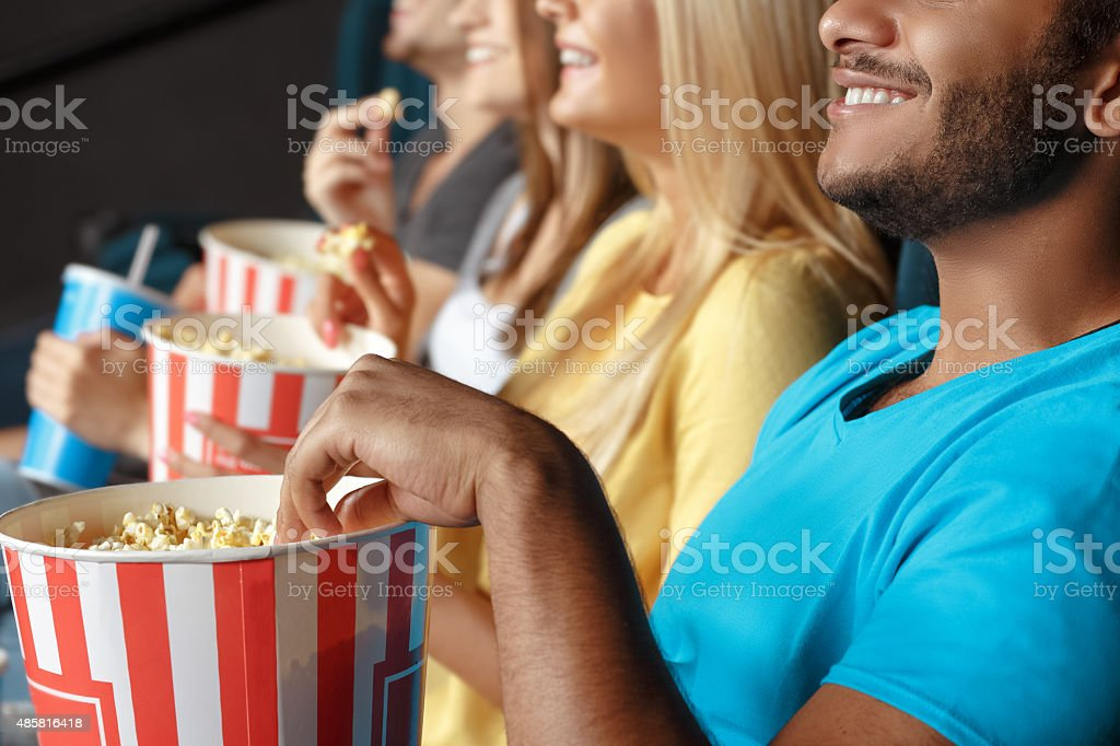 Friends eating popcorn at the movie theatre stock photo