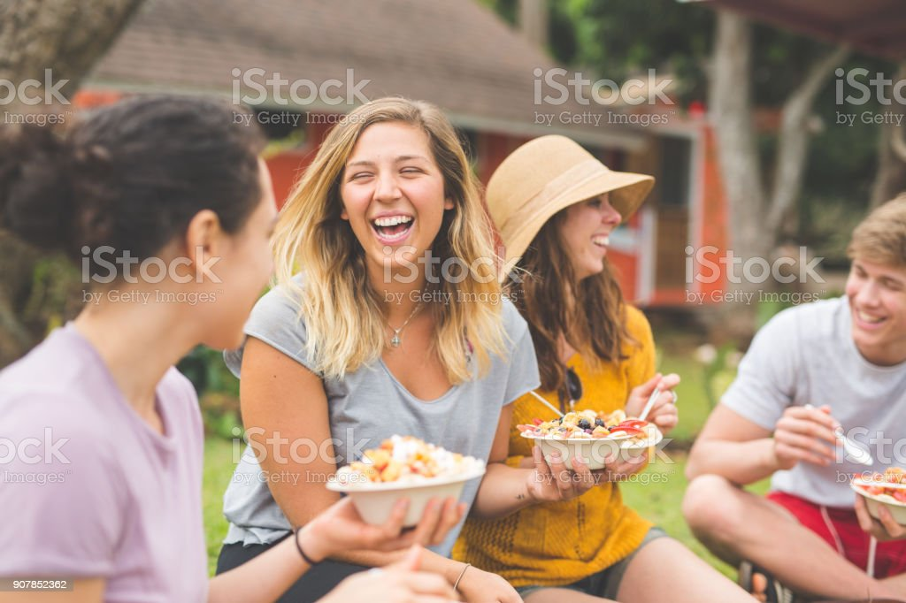 Friends eating smoothie bowls topped with fresh tropical fruit stock photo