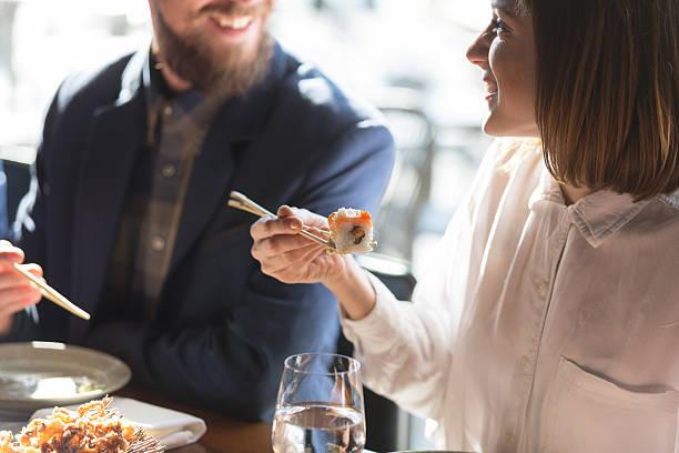 freunde essen sushi - sushi essen stock-fotos und bilder