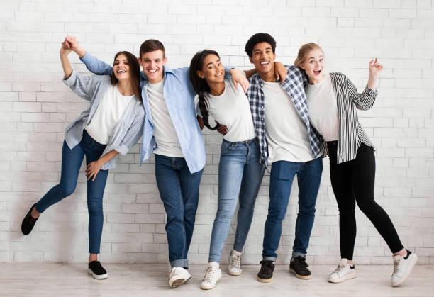 vrienden omarmen en plezier hebben over witte bakstenen muur - model beroep stockfoto's en -beelden