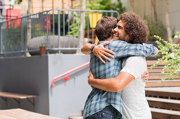 Friends embracing each other Cheerful best friends embracing each other outside coffee shop. Two young multiethnic guys hugging each other. Happy smiling best friends meeting each other after a long time with a hug. brother stock pictures, royalty-free photos & images