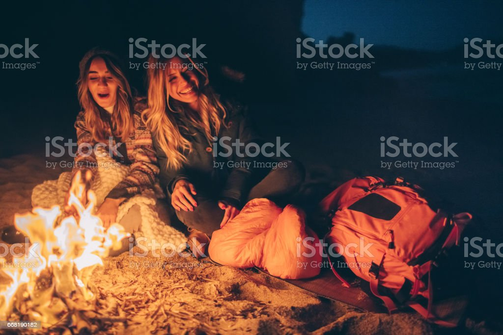 Friends enjoy evening on the beach by the log fire stock photo