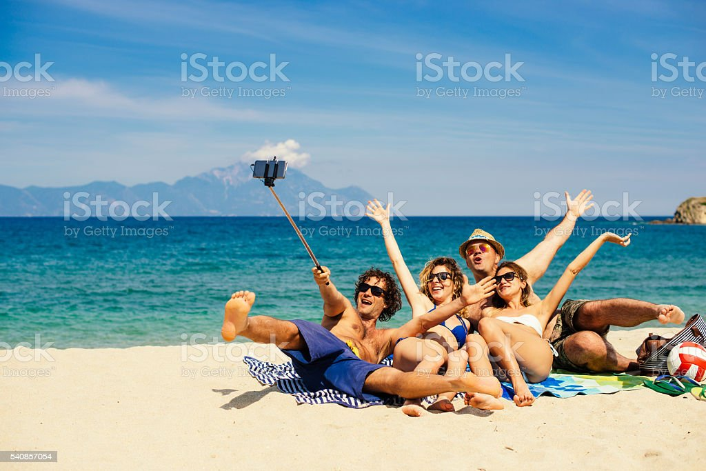 Friends enjoy holidays on Greek beach in Aegean sea stock photo
