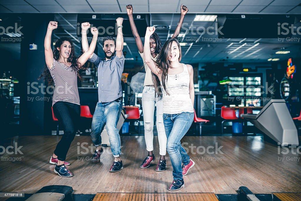 Friends enjoy playing bowling stock photo