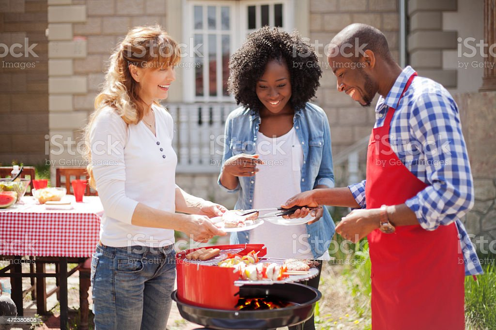 Friends enjoying a barbecue on a sunny day stock photo