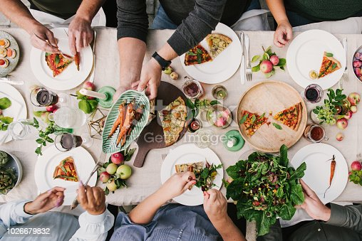Friends enjoying a dinner together in greenhouse harvest party photo of group of people eating, photo taken overhead table top shot