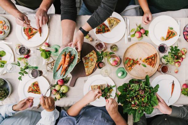 parte de la cosecha de amigos disfrutando de una cena juntos en invernadero - vegana fotografías e imágenes de stock
