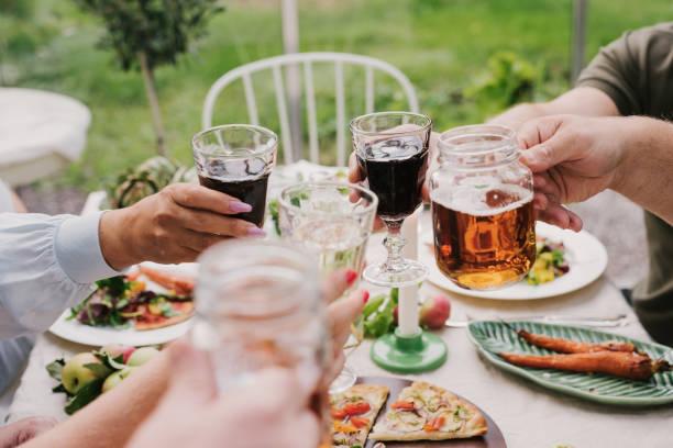 freunde genießen ein abendessen zusammen rösten in wein und bier - bier gesund stock-fotos und bilder