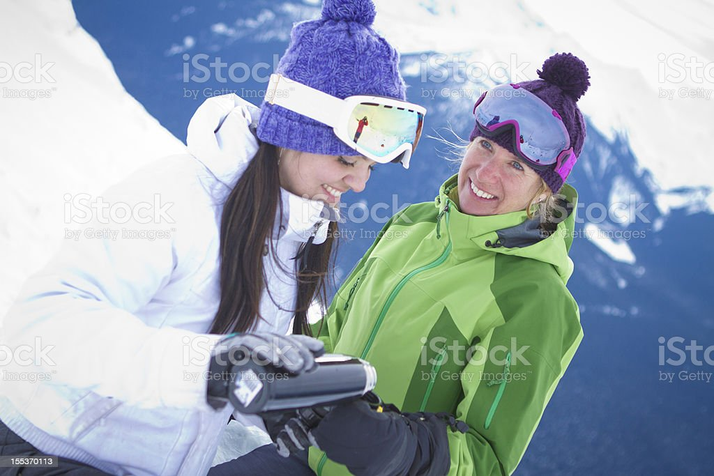 Friends enjoying a hot drink at top of mountain. royalty-free stock photo
