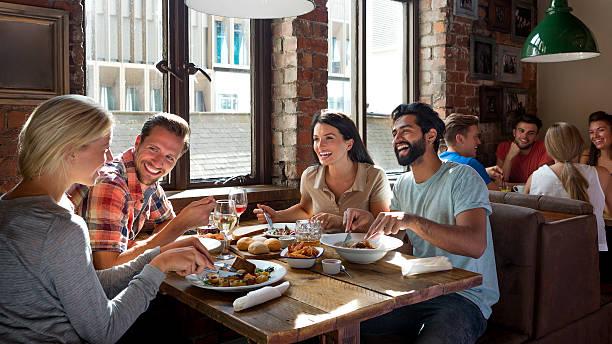amigos disfrutando de una comida - restaurante fotografías e imágenes de stock