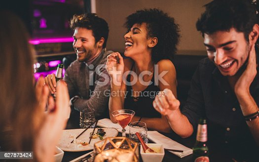 Group of friends enjoying a late evening meal in a restaurant.