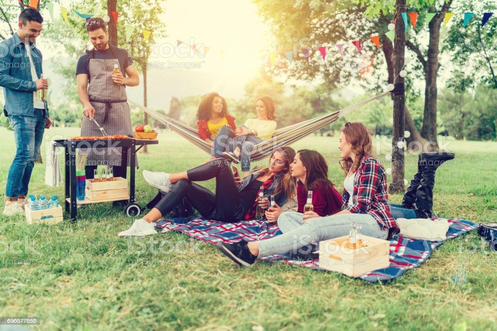 Vrienden genieten van een picknick met barbecue in het park foto