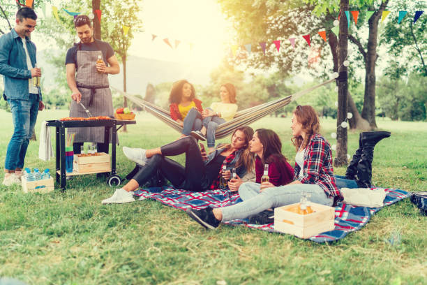 Friends enjoying a picnic with barbecue in the park stock photo