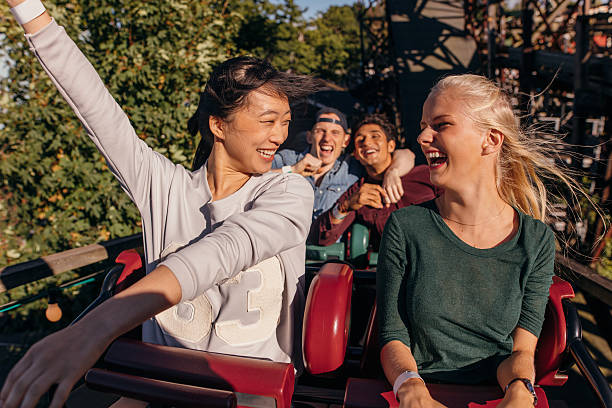Friends enjoying and cheering on roller coaster – Foto