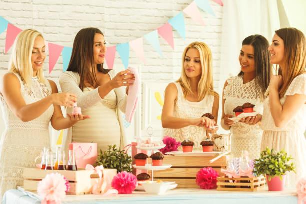 amigos disfrutando de babyshower partido de alimentos y bebidas - baby shower fotografías e imágenes de stock