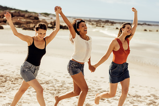 Happy women friends walking together on beach holding hands. Three young women enjoying and dancing together on a beach vacation.