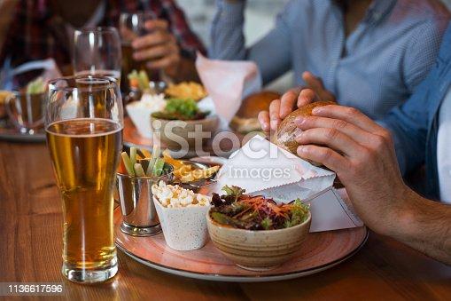 istock Friends enjoying beer and burgers in bar 1136617596