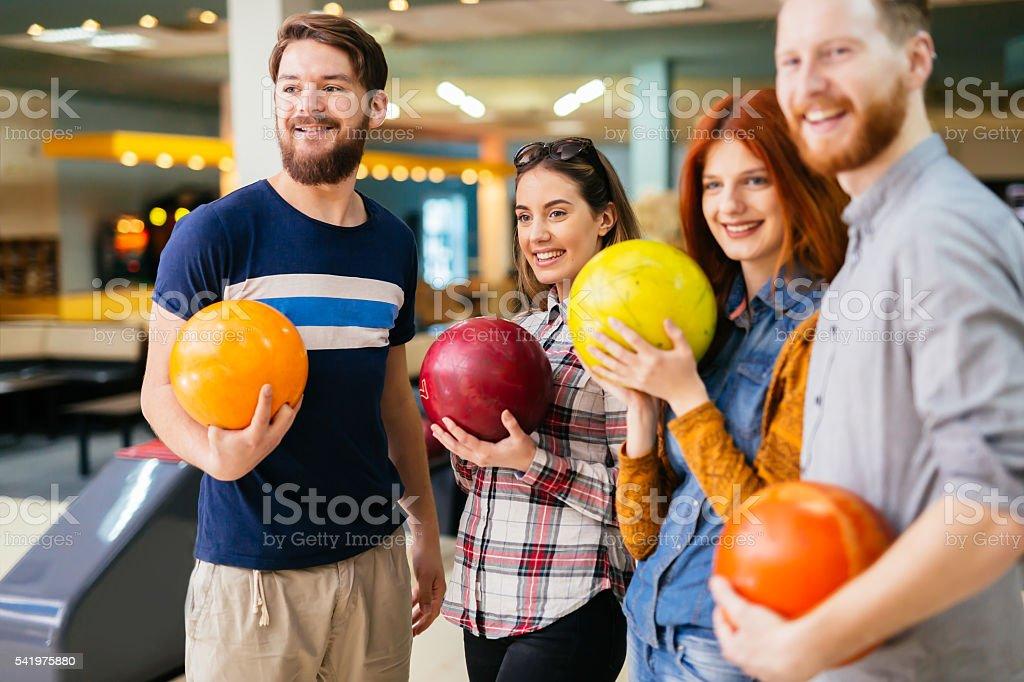 Friends enjoying bowling at club stock photo