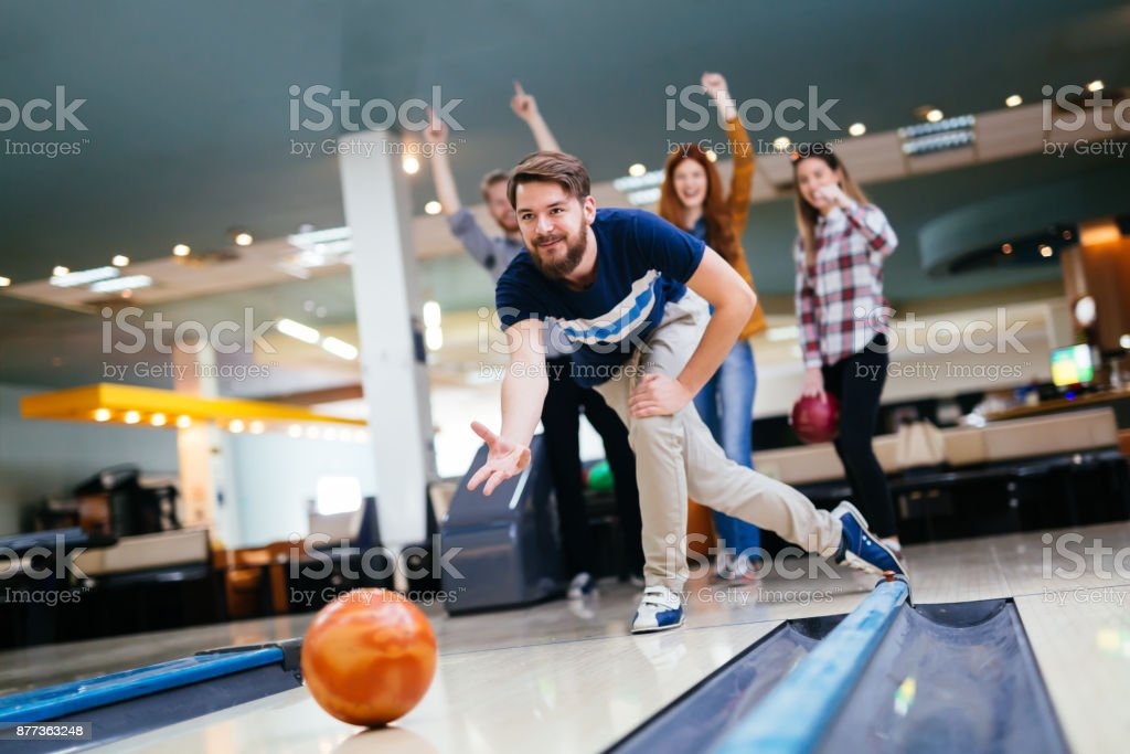 Friends enjoying bowling at club stock photo