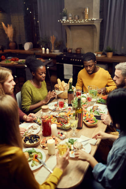 friends enjoying dinner at home - family gatherings stock pictures, royalty-free photos & images