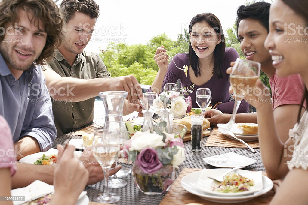 Friends Enjoying Dinner Party Outdoors stock photo